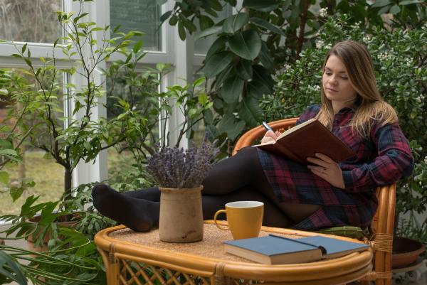 Junge Frau schreibt ihr Tagebuch im Wintergarten
