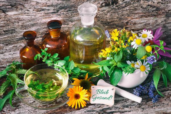 Kraeutertee mit Medizinflaschen und heilenden Kraeutern im Moerser