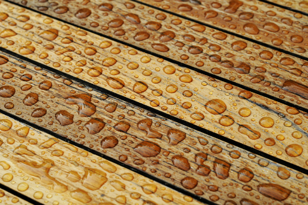 Nasses Holz mit perlenden Wassertropfen