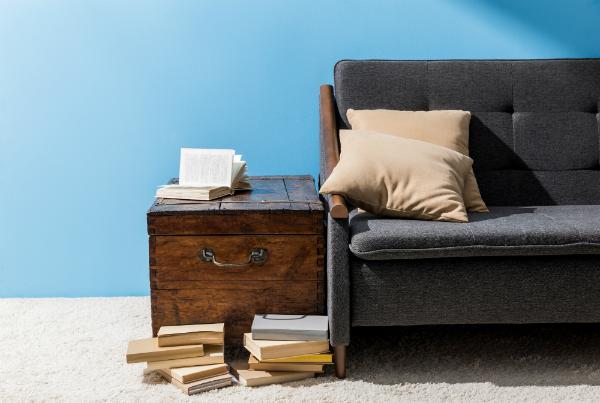 Hoelzerne Truhe mit Buechern nahe Couch vor blauer Wand
