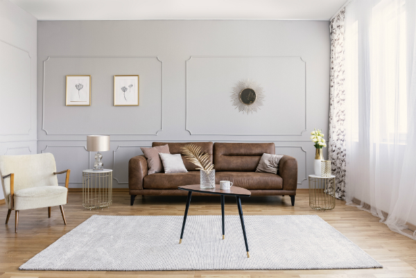 Minimalistische Einrichtung des Wohnzimmers mit brauner Ledercouch