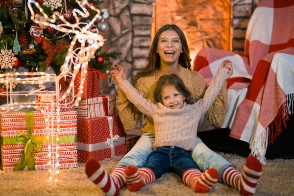 Kleines Maedchen mit Mutter im dekorierten Wohnzimmer zu Weihnachten