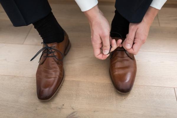 Mann schnuert Schuhe