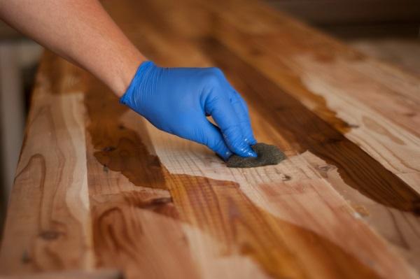 Mit einem feuchten Schwamm wässert ein Mann ein Möbelstück Holzwachs anwenden