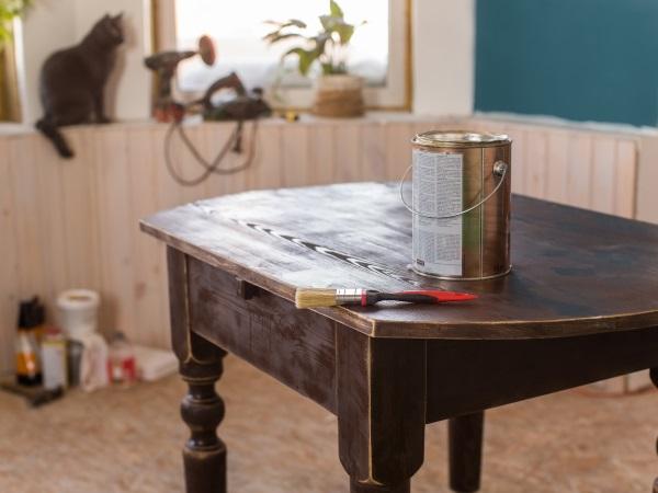 Auf einem Holztisch steht ein kleiner Eimer Holzwachs, davor liegt ein Pinsel Holzwachs anwenden
