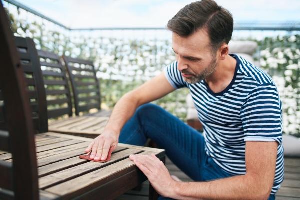 Ein Mann schleift einen Holzstuhl mit Schmirgelpapier ab Holzwachs anwenden