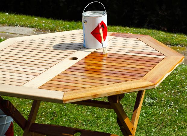 Gartentisch wird mit Pinsel eingeölt