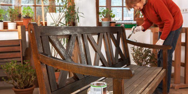 Frau behandelt eine Gartenbank mit Holzwachs