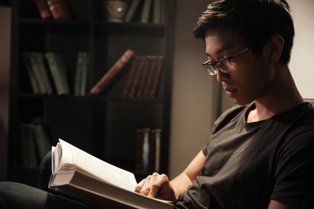 Junger Mann liest Buch - eine Gemütliche Leseecke einrichten muss nicht kompliziert sein