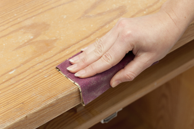Holz wird mit Schleifpapier behandelt