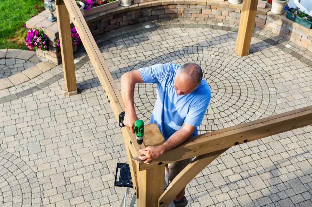 Mann schraubt Holzleisten eines Gartenpavillons zusammen