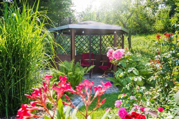Gartenpavillon umgeben mit Grünpflanzen und Blumen -den Gartenpavillon gestalten ist wichtig