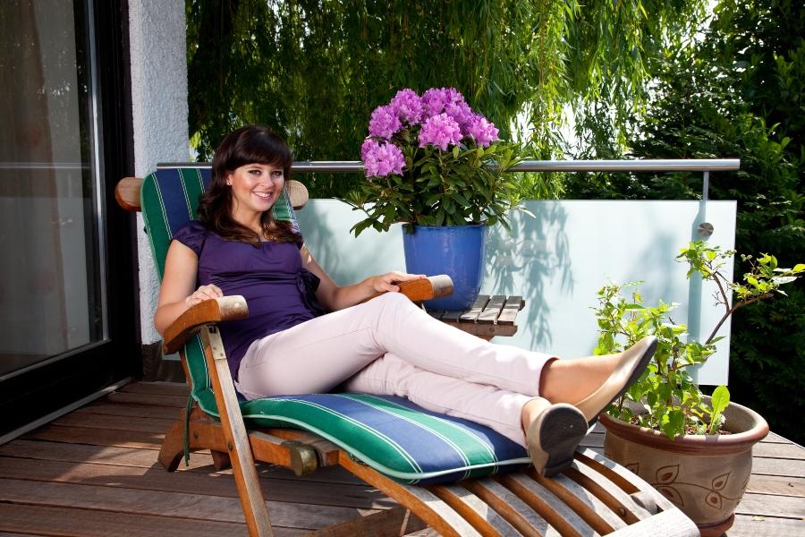Junge Frau sitzt im Liegestuhl Sonnenliegen