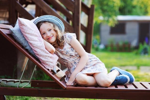 Mädchen liegt auf Gartenliege