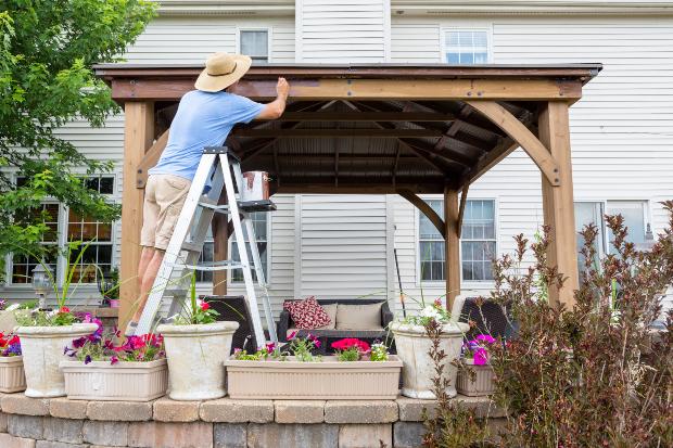 Mann streicht Holzlatten eines Gartenpavillons
