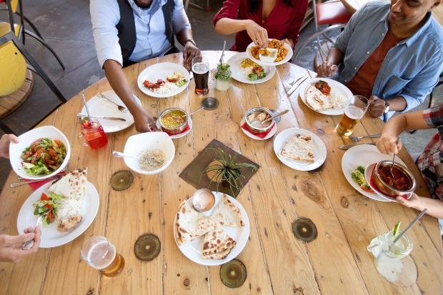 Menschen essen am runden Esstisch aus Holz