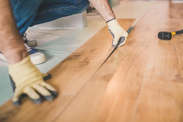 Mann verlegt Laminatboden in Holzoptik - dies ist kein Echtholz