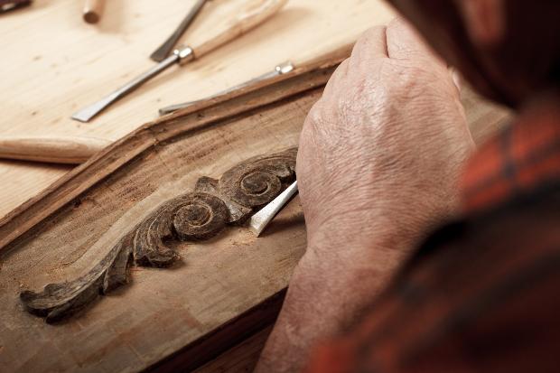 Ein Tischler arbeitet an dem Ornament eine Holzmöbels