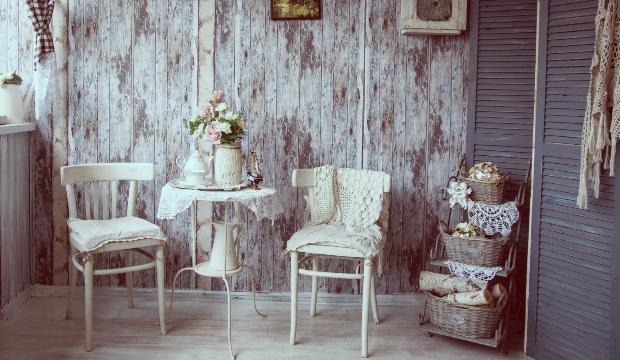 Eine Küche mit zwei Stühlen im Landhausstil, auf dem Tisch stehen frische Blumen und Körbe sind als zusätzliches Deko-Element aufgestellt Landhausdeko für Haus und Garten