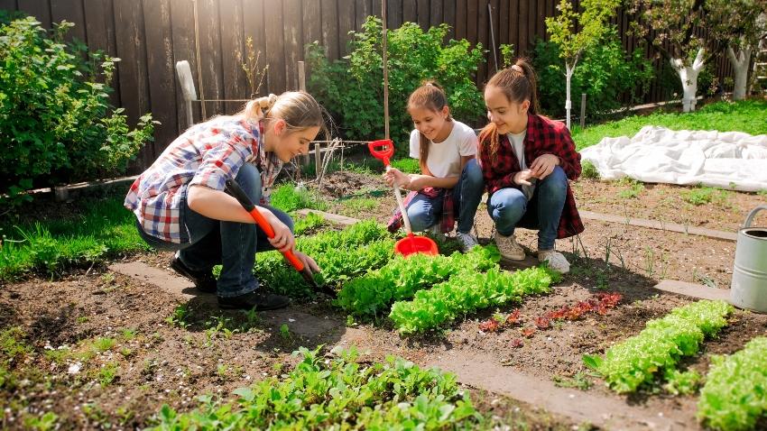 Frau mit 2 Töchtern bei der Gartenarbeit - Gartenbeet dekorieren und einrichten