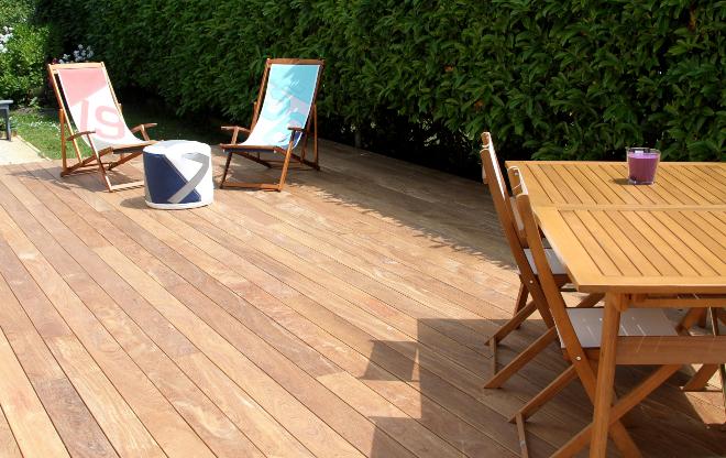 Holzterrasse mit Sitzgruppe und Liegestühlen