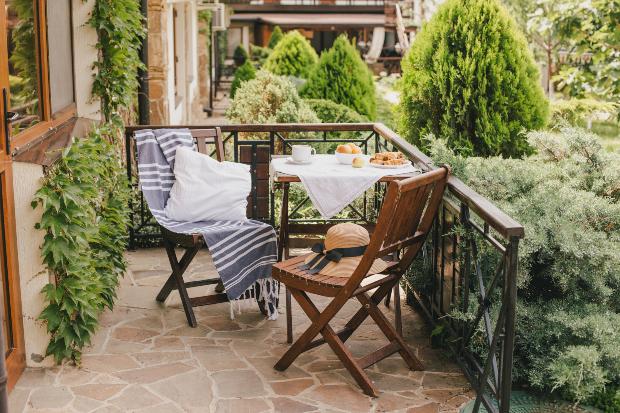 Ein einladender Holztisch, flankiert von zwei Holzstühlen, ist auf einem Balkon positioniert. Die Szenerie ist umgeben von zahlreichen Pflanzen. Terrassenlounge im Landhausstil