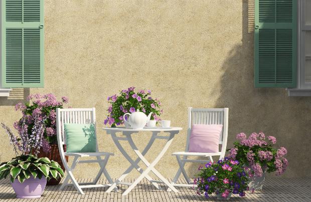 Umgeben von Zierpflanzen steht ein filigraner Holztisch im Landhausstil, daneben sind zwei Holzstühle platziert, die zum Verweilen einladen. Terrassenlounge im Landhausstil