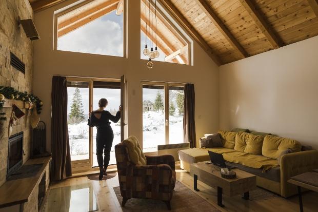 Frau schaut aus dem Haus - Stilvoll einrichten mit antiken Möbeln