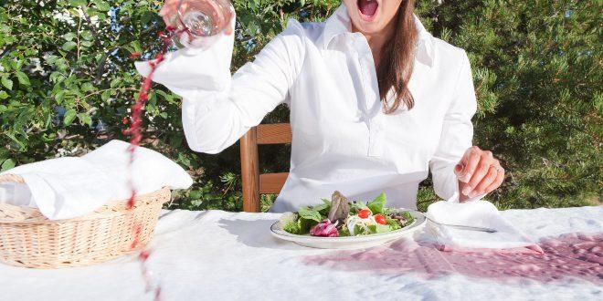 Frau verschüttet Rotwein am Tisch - Rotweinflecken vom Holztisch entfernen