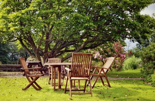 Gartenmöbel unter einem Baum - Holz im Garten