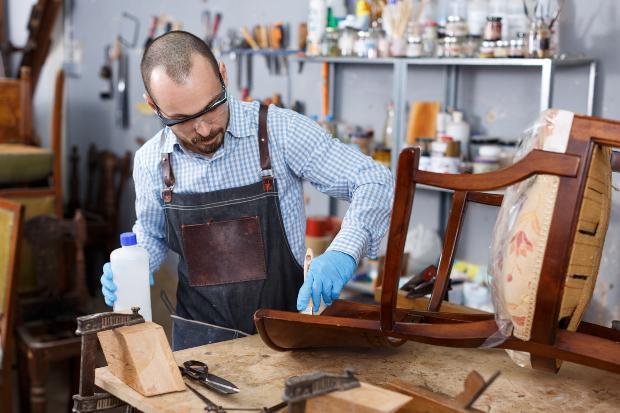 Mann behandelt einen antiken Stuhl mit Pflegemittel